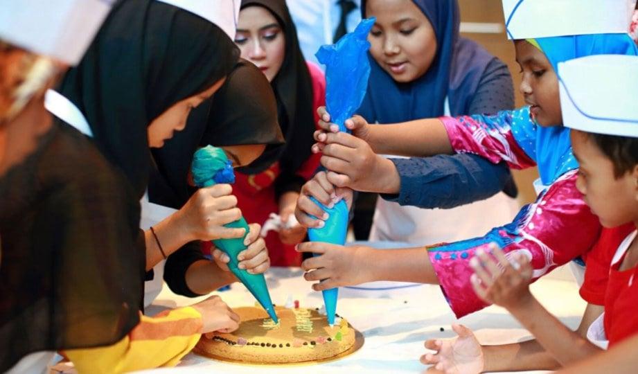 KANAK-kanak Living Hope dan Yayasan Generasi Gemilang menghias biskut raksasa .