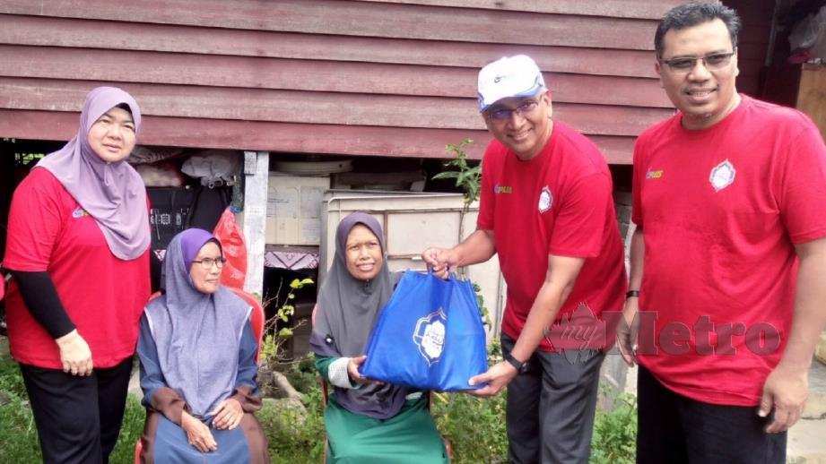 Azman (dua kanan) bersama Tuan Mohd Asri (kanan) menyampaikan sumbangan kepada ibu tunggal, Hamidah Ismail, 51, pada Program TKHM bersama PLUS hari ini. FOTO Rosman Shamsudin