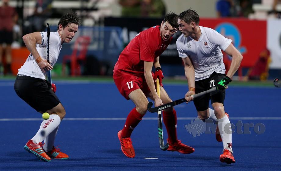 PEMAIN Poland, Maciej Trojanek (tengah) cuba melepasi pemain Kanada di Ipoh. — FOTO Effendy Rashid
