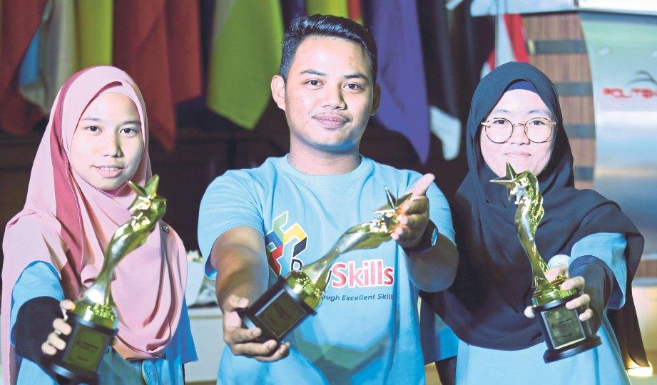 NORAZAH (kiri), Aiman dan Ainul Mahfuzah bersama anugerah yang diterima pada majlis Anugerah PolySkills 2018.