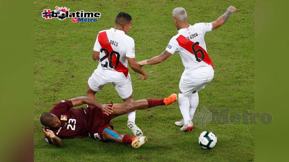 Pemain Venezuela, Salomon Rondon (23) berebut bola dengan dua pemain Peru, Edison Flores (kiri) dan Miguel Trauco. FOTO REUTERS