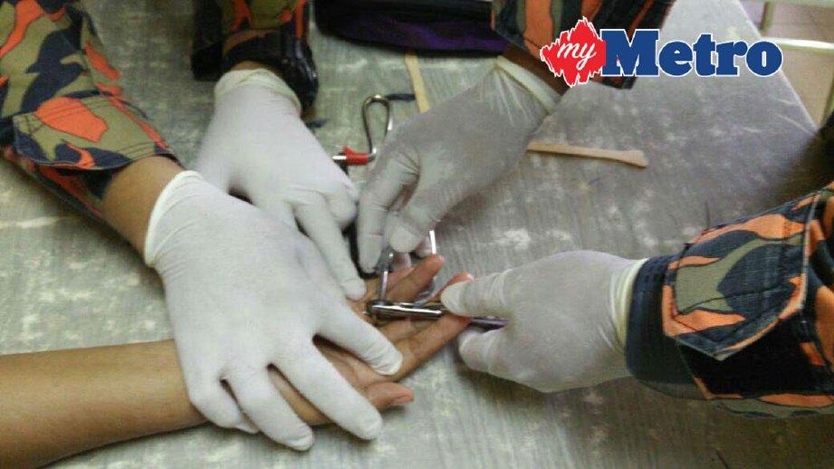 Anggota bomba memotong cincin yang tersekat di jari manis wanita berusia 39 tahun hari ini. FOTO ihsan bomba