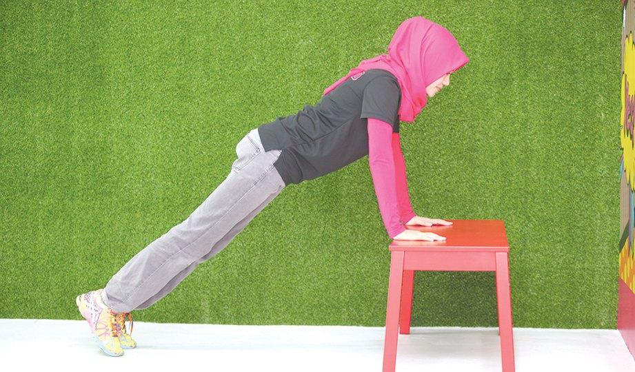 1. PASTIKAN bangku dipilih kukuh dan berat untuk keselamatan. Letakkan kedua-dua tangan pada bangku dan biarkan sedikit berat badan anda berada pada bangku itu. Jarakkan kaki ke belakang sehingga badan anda kelihatan sedang membuat plank. Buka kaki selebar pinggul anda.