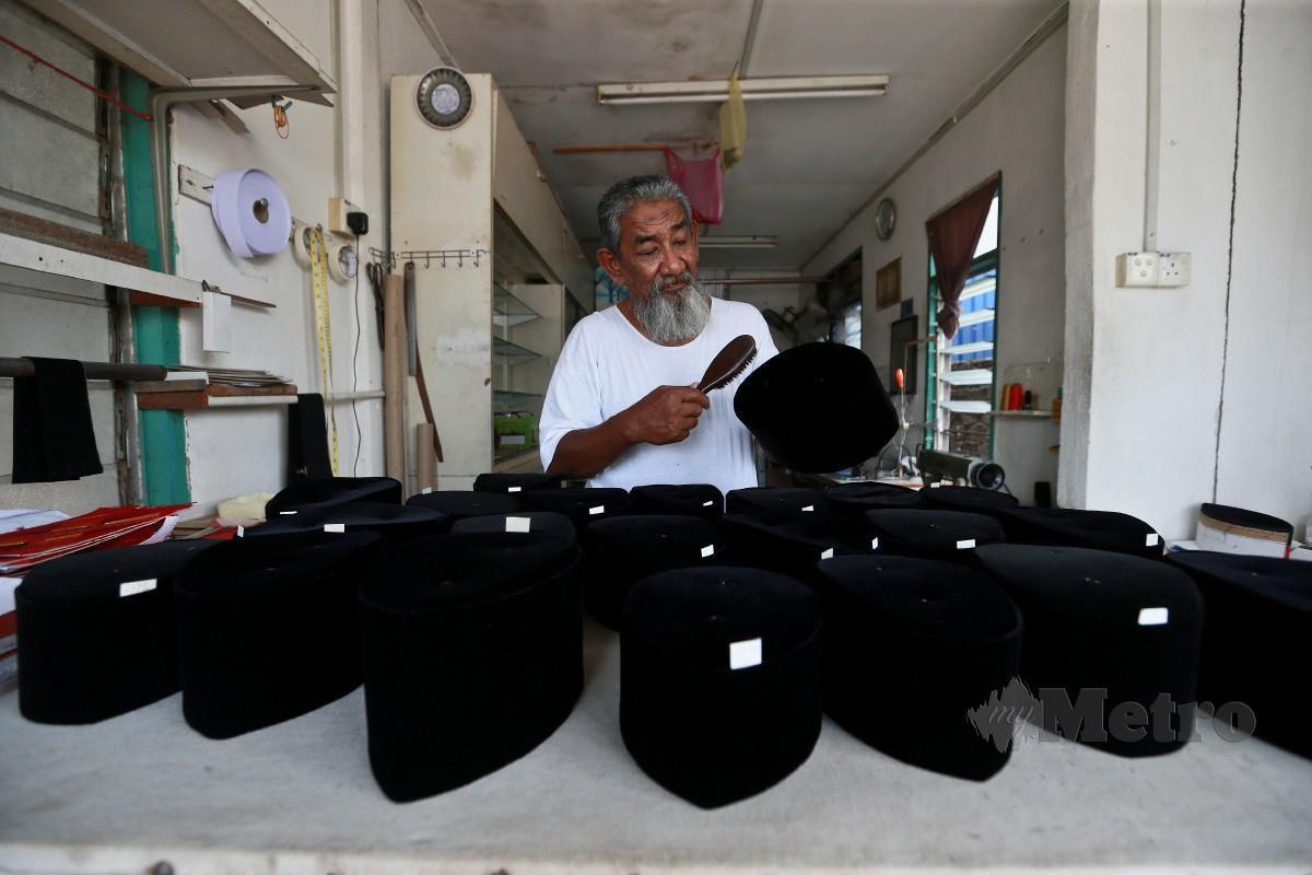 Adnan  tekun menyiapkan tempahan songkok tradisional untuk dijual kepada pelanggan menjelang perayaan Hari Raya Aidilfitri dikedainya, Kampung Losong. FOTO GHAZALI KORI
