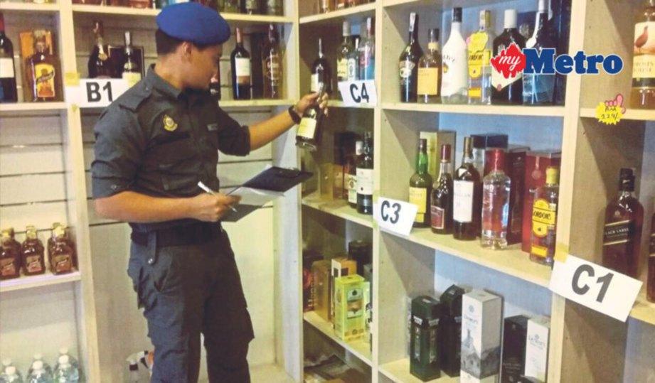 ANGGOTA Penguat kuasa KPDNKK meneliti label minuman keras yang dipercayai tiruan.