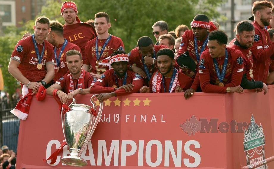 KAPTEN Liverpool, Jordan Henderson dan penyerang Origi memegang trofi Piala Eropah dalam perarakan di sekitar bandaraya Liverpool, awal pagi tadi. — FOTO AFP