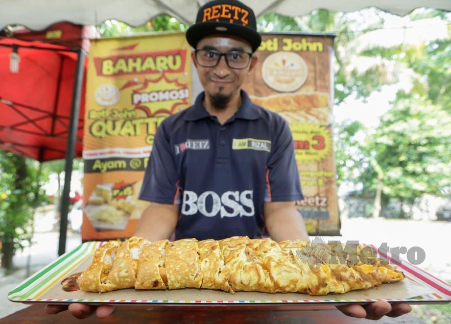 MOHD Rizal memperkenalkan menu istimewa kafenya di Roti John Reetz Bella. Foto Hafiz Sohaimi