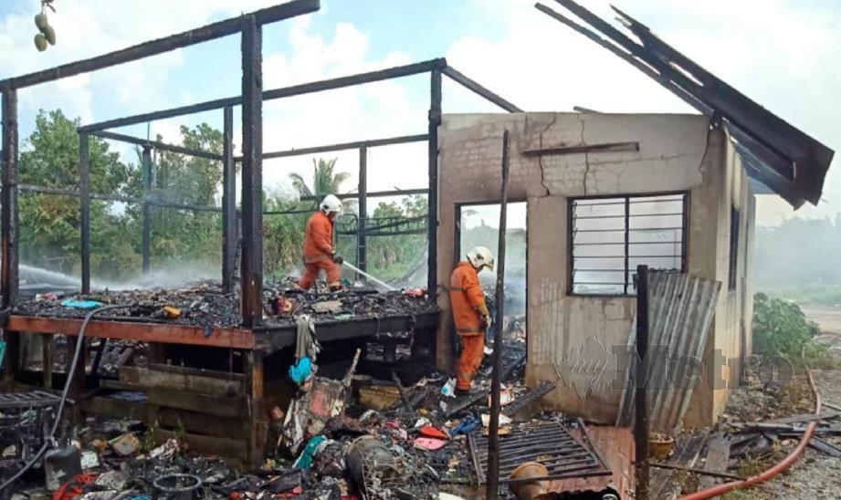ANGGOTA bomba memadam kebakaran rumah didiami Rozila dan keluarganya di Kampung Sungai Rengas, Kuala Terengganu, hari ini. FOTO ihsan bomba.