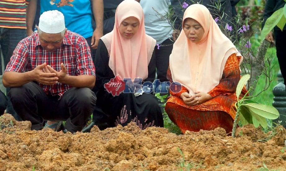 Aziz dan Zalina mengaminkan doa di pusara anak mereka. FOTO Azhar Ramli