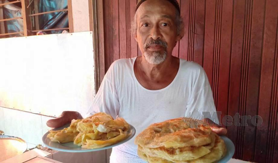 MAT Ali menunjukkan roti canai yang dijualnya. FOTO Ahmad Rabiul Zulkifli