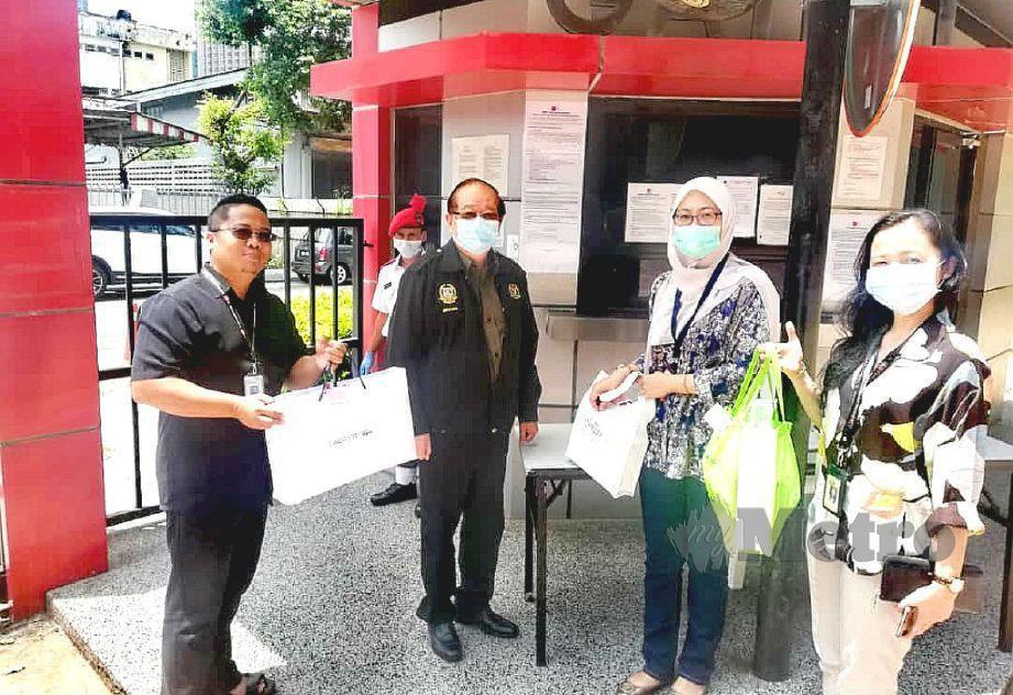 MICHEAL Chong ( dua dari kiri ) menyampaikan sumbangan penutup mulut dan hidung kepada wakil media The New Straits Times Press (Malaysia) Berhad semalam.