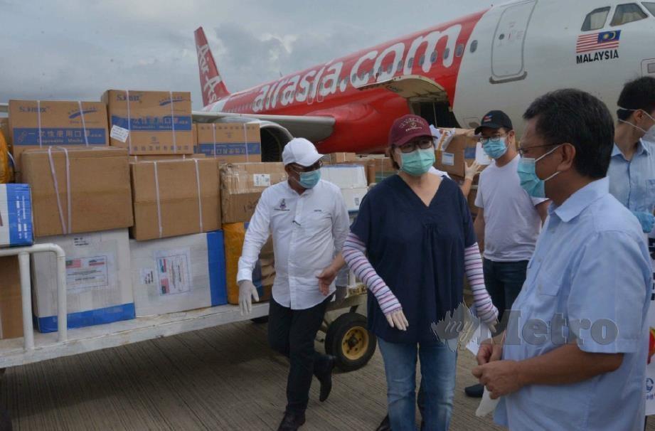 MOHD Shafie Apdal (kanan) meninjau peralatan yang tiba. FOTO YUN MIKAIL