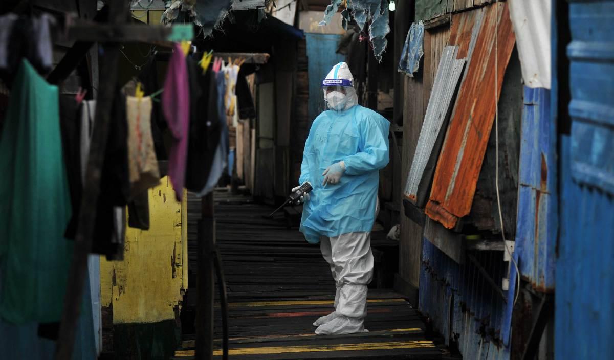 ANGGOTA PDRM memakai pakaian perlindungan diri (PPE) ketika melakukan pemantauan di Kampung Saguking. FOTO BERNAMA