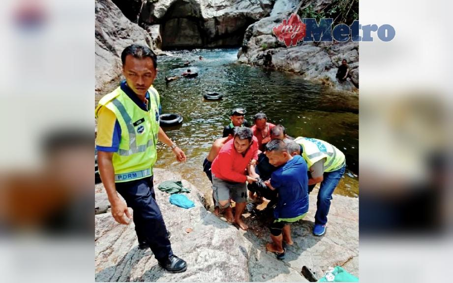 Penduduk kampung membantu anggota polis mengangkat dua sahabat yang lemas ketika mandi kawasan air terjun Lubuk Kain, Kampung Syukur. FOTO Rosli Ilham