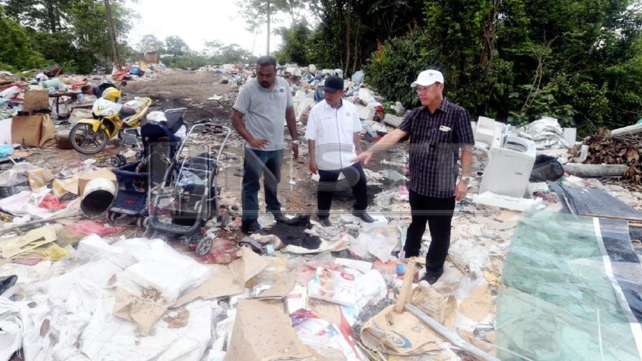 Syed Othman (tengah) bersama Tan Peng Chye (kanan) melihat sampah yang dibuang di tapak pembuangan sampah haram di Kota Puteri, Masai. FOTO Hairul Anuar Rahim