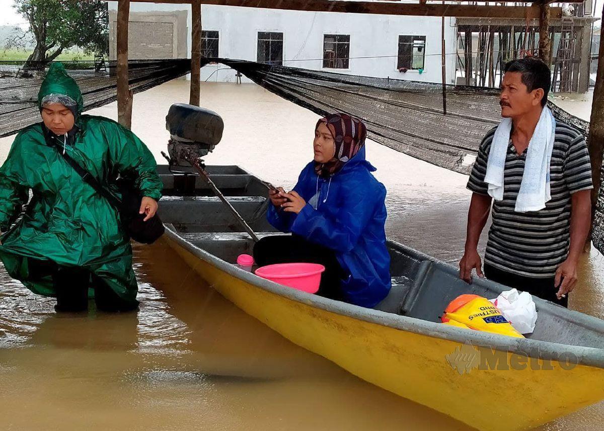 WAN Abdullah (kanan) bersama keluarganya menaiki perahu atau bot sebagai pengangkutan utama di musim tengkujuh. FOTO NIK ABDULLAH NIK OMAR