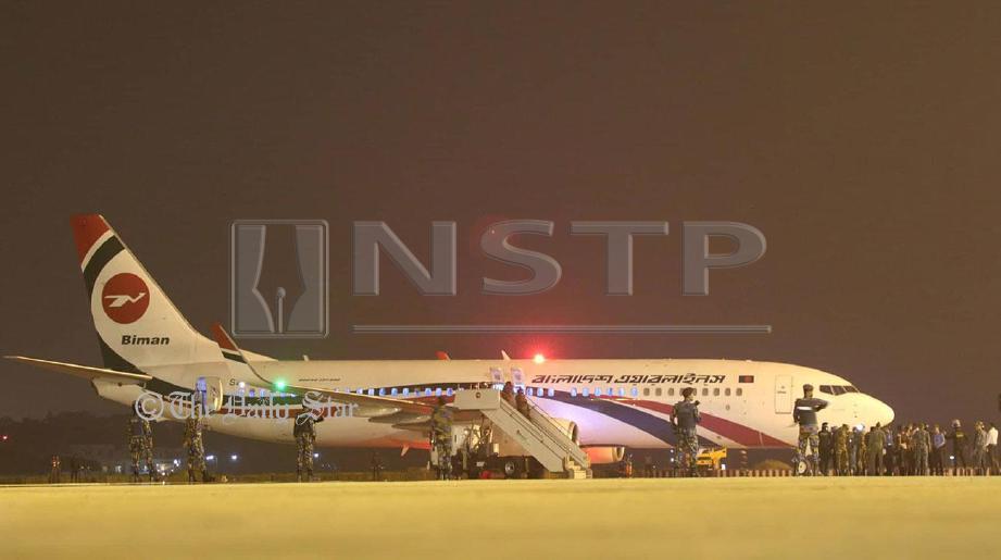 ANGGOTA keselamatan, termasuk komando mengawal sekitar pesawat Boeing 737-800 yang mendarat cemas di Chittagong selepas cuba dirampas. - Foto Twitter