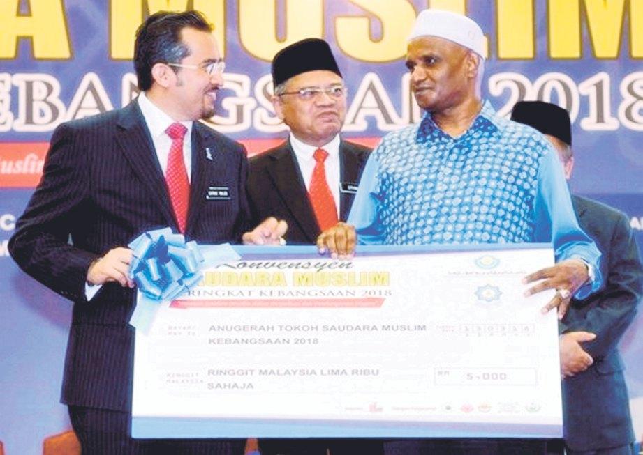 AMRAN (kanan) menerima anugerah disampaikan Dr Asyraf Wajdi.