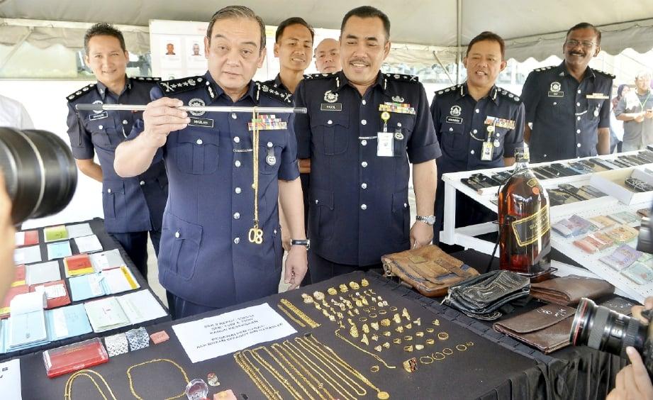 MAZLAN (dua dari kiri) menunjukkan antara barang kes dirampas daripada dua kumpulan kongsi pada sidang media di IPK Selangor, Shah Alam, hari ini. FOTO Faiz Anuar