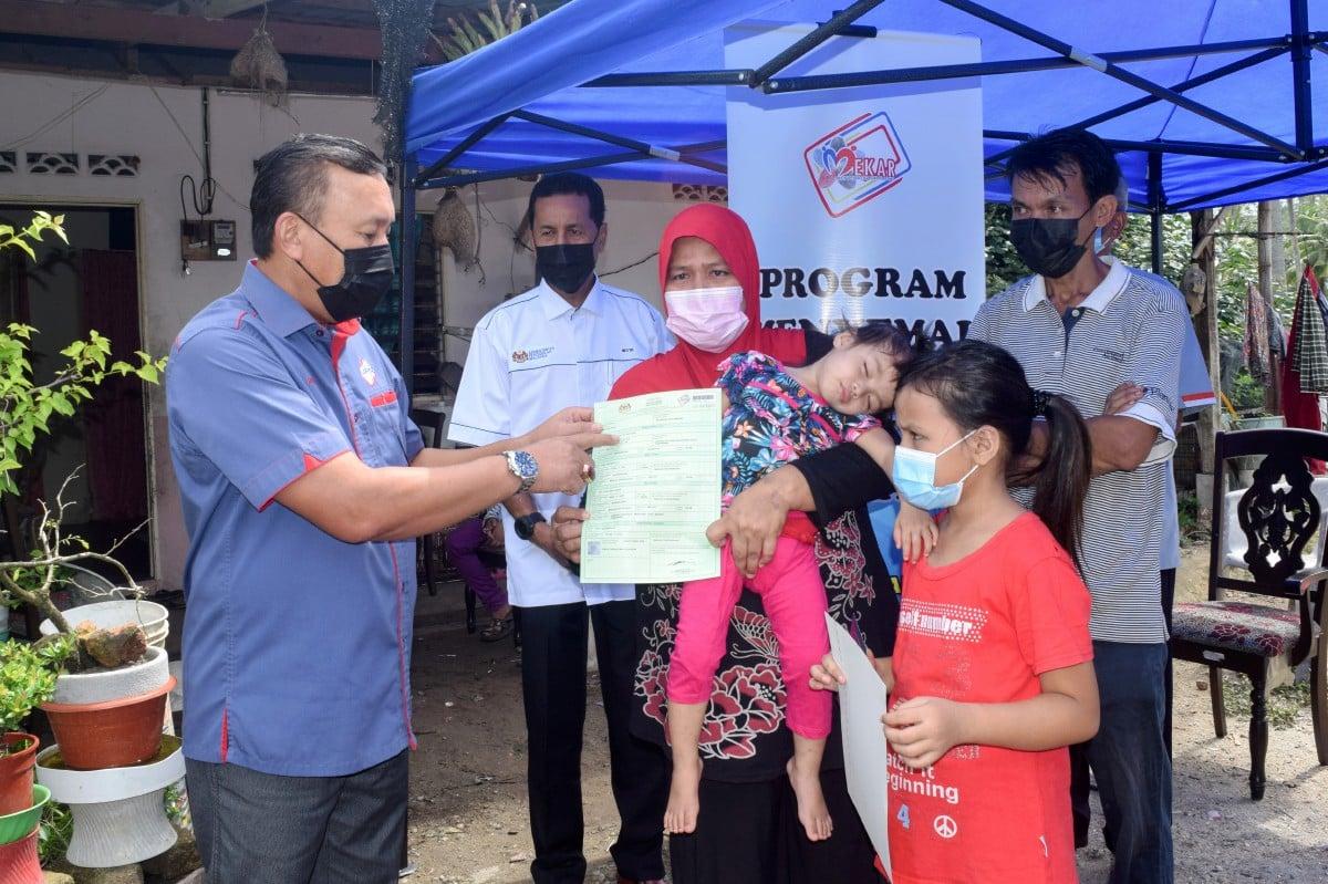 Ruslin (kiri) menyerahkan sijil kelahiran Nur Iffika Dahlia Rusli, 9, (dua daripada kanan) dan Nur Irine Delisha, 2, sambil diperhatikan ibu bapa mereka Rusli Abdullah, 45, (kanan) serta Bibi Sopiar Jusoh, 43, pada Program Menyemai Kasih Rakyat (Mekar) di Kampung Gong Balai, Merchang hari ini. FOTO BERNAMA