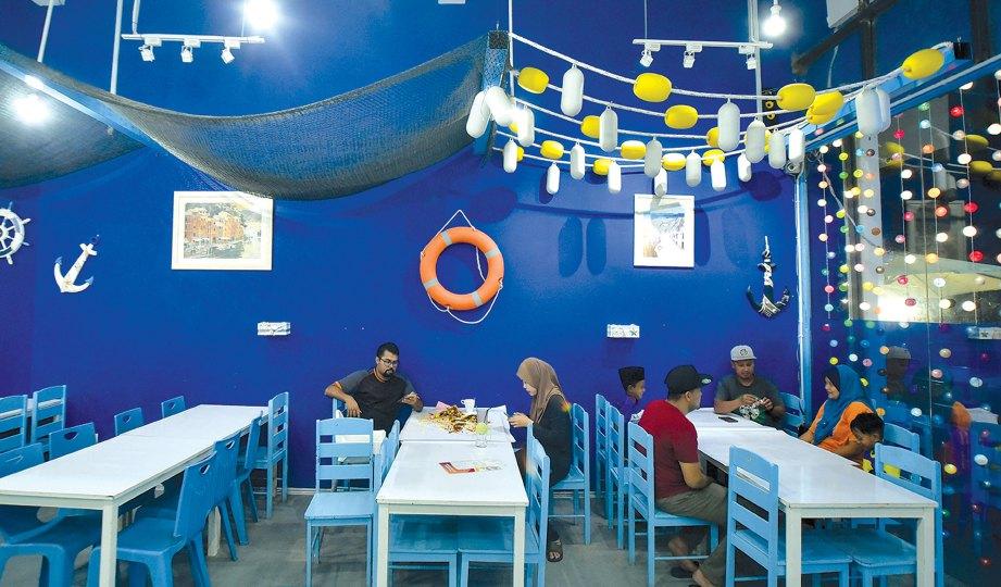 SUASANA restoran yang dihias seperti berada di tepi pantai.