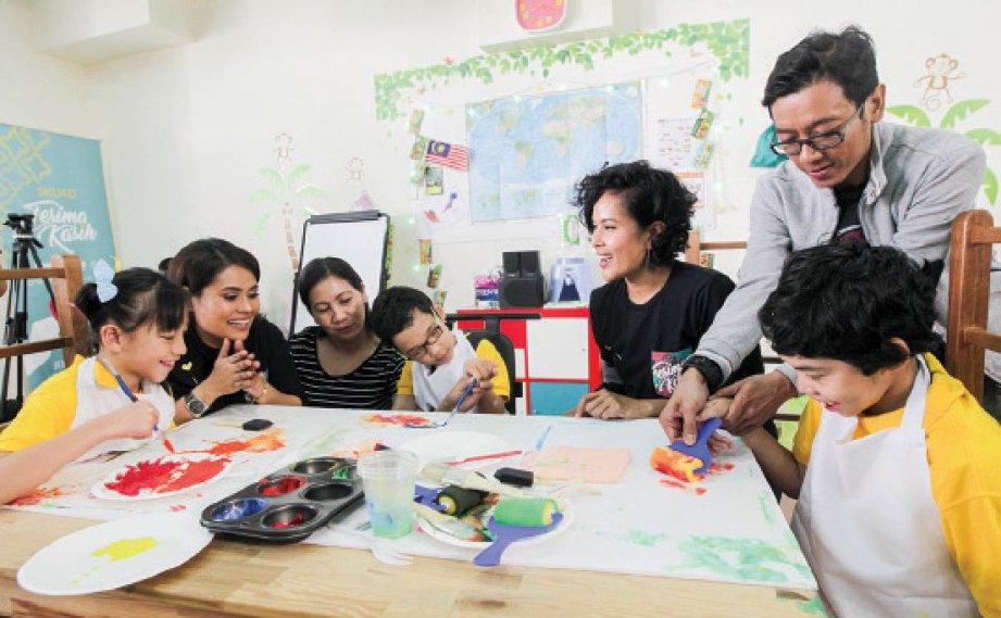 FIZA Sabjahan (dua kiri) melihat hasil lukisan kanak-kanak palsi serebrum.