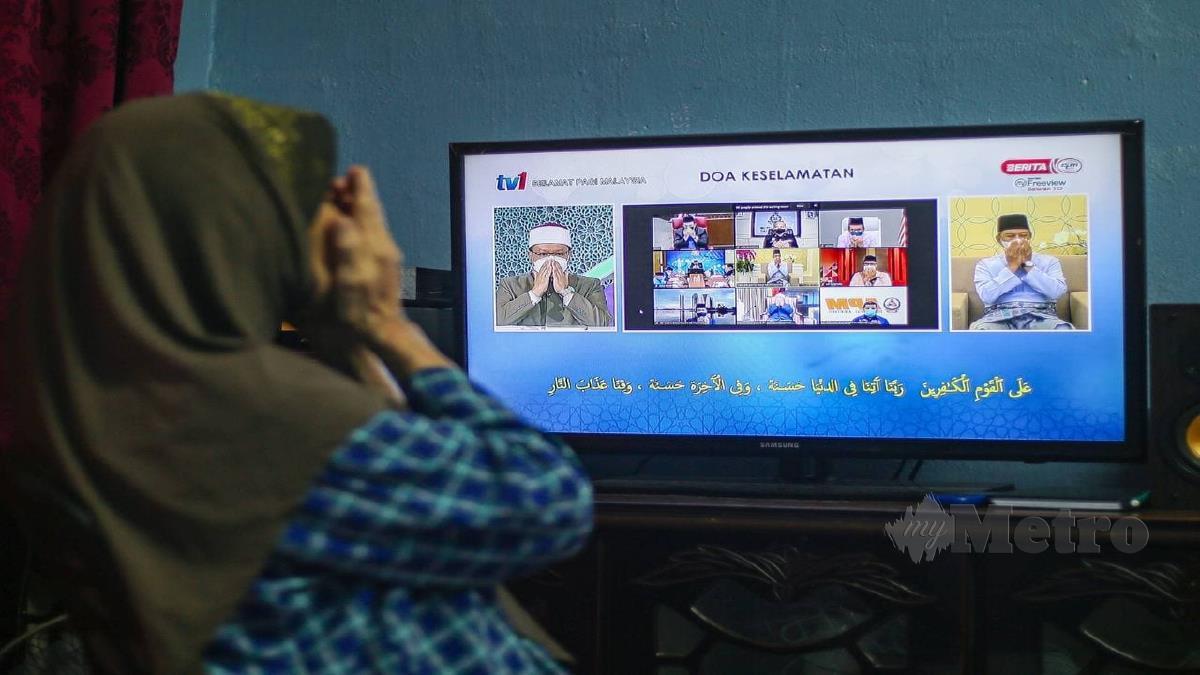 SAFTIAH Hassan, 72 mengaminkan doa dibacakan  ketika mengikuti  Program Mega  PKRC Berselawat bersama Perdana Menteri dan rakyat secara maya di TV1. FOTO Aswadi Alias.