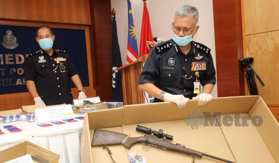 HASANUDDIN menunjukkan satu laras senapang dilengkapi penyenyap bunyi yang dirampas dalam serbuan di sebuah rumah Kampung Banggol Merbol Gua Sitok,  Rantau Panjang ketika sidang media di IPK Kelantan. FOTO Nik Abdullah Nik Omar