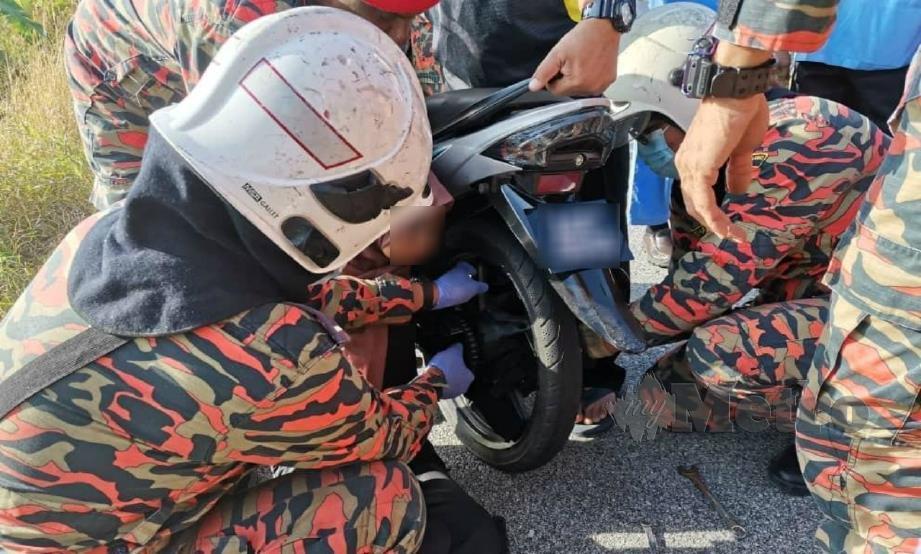 Anggota bomba membantu mengeluarkan tangan mangsa yang tersepit. FOTO Ihsan Bomba.