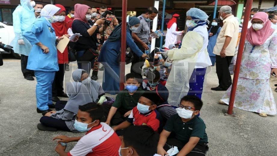 PASUKAN perubatan memberi bantuan awal kepada pelajar yang terhidu bahan kimia di SMK Pasir Putih, Pasir Gudang. FOTO Hairul Anuar Rahim