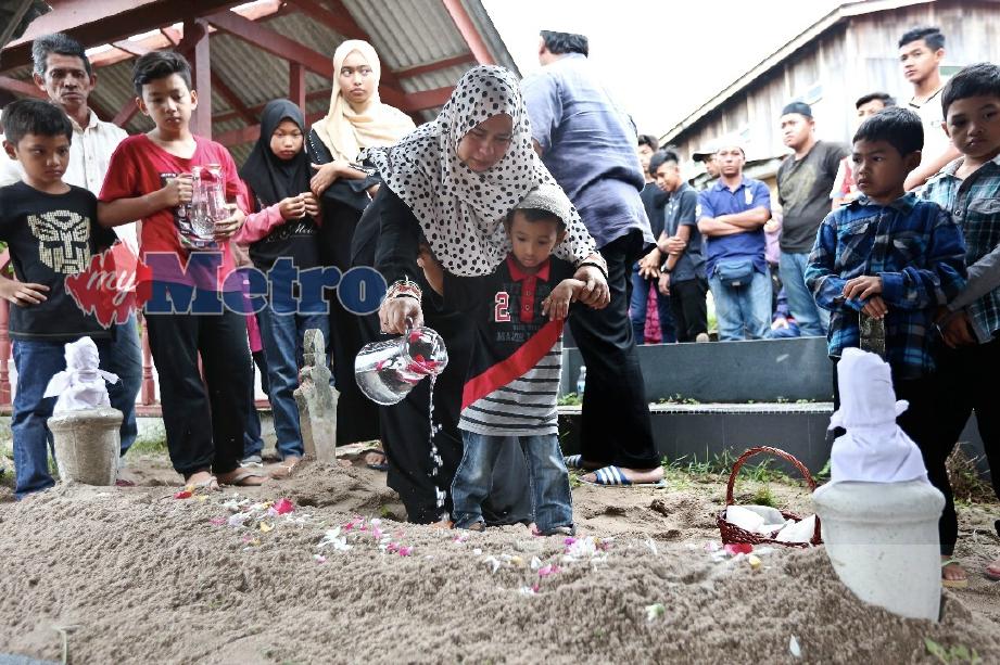 Tengku Mastura Tengku Mohamad, 35, isteri Ahmad Fakhrurazi bersama anaknya, Muhammad Aqil Harith semasa pengebumian jenazah Allahyarham suaminya di Tanah Perkuburan Islam Gong Pauh, Kuala Ibai. FOTO Ghazali Kori