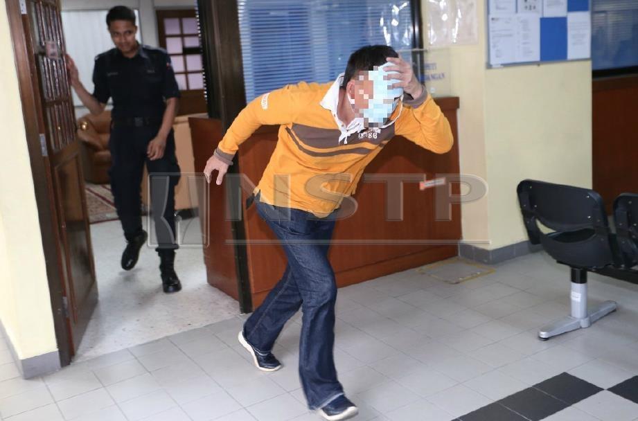 Bekas sarjan tentera cuba mengelak dari gambarnya dirakam jurugambar selepas dijatuhi hukuman penjara 24 tahun dan 15 sebatan oleh Mahkamah Sesyen Johor Bahru. FOTO Mohd Azren Jamaludin