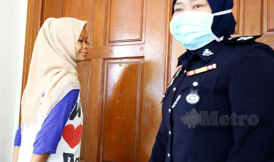 ANGGOTA polis mengiringi Nursahira di Mahkamah Sesyen Alor Setar. FOTO Amran Hamid