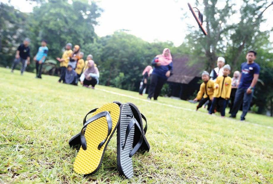 KANAK-KANAK mencuba permainan baling selipar. FOTO Mohd Hairul Helmy Mohd Din