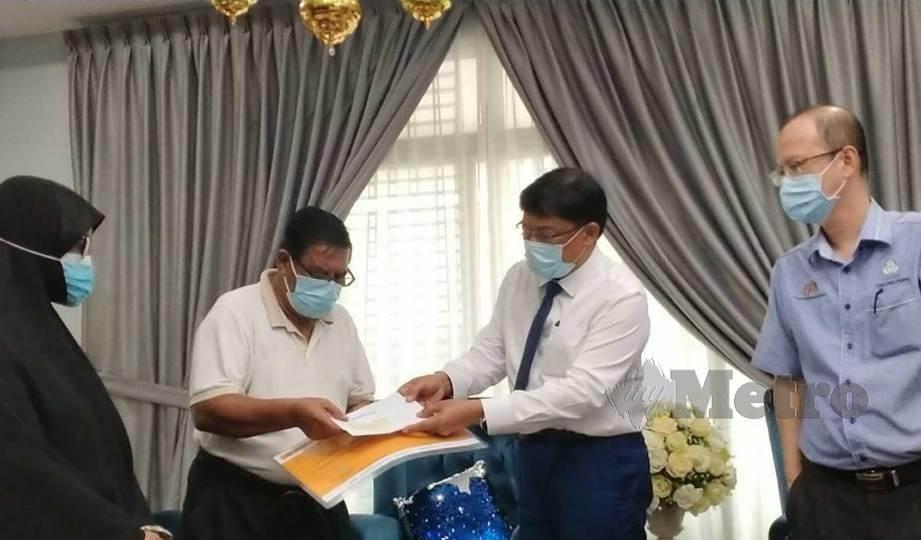 MOHD Izhar (dua kanan) menyampaikan sumbangan faedah pengurusan jenazah sebanyak RM2,000 kepada bapa pencarum, Abd Rahman di kediaman mereka.  FOTO Omar Ahmad