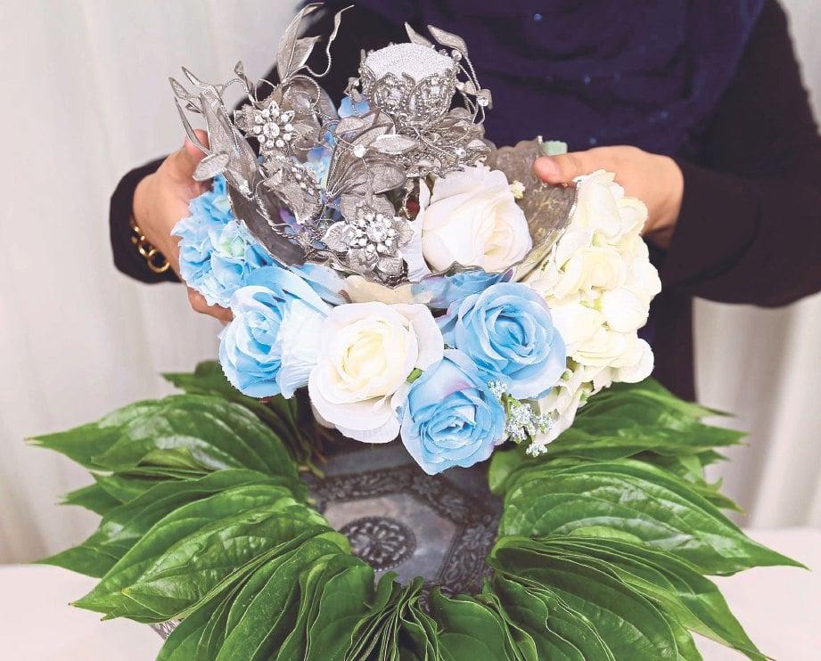 5. LETAKKAN gubahan bunga yang disusun di atas dulang hantaran. Di atasnya diletakkan bekas cincin dengan hiasan kerawang.