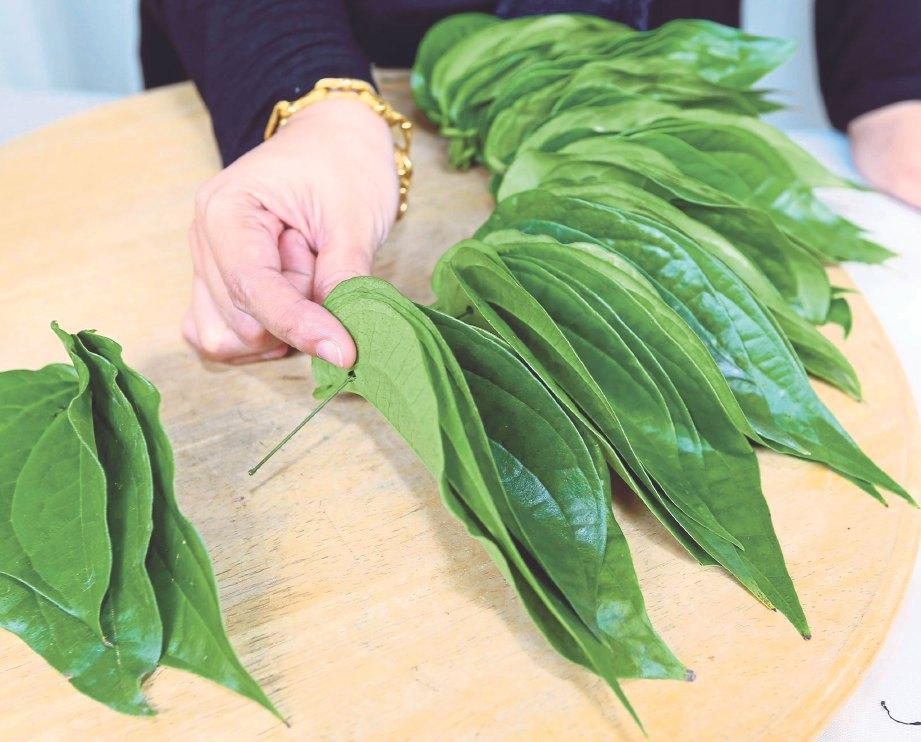 2. AMBIL tiga helai daun sirih, susun berlapis dan cucuk pada dawai. Susun mengelilingi dawai sehingga mendapat bentuk bulat seluas dulang hantaran.