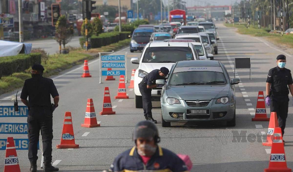 ANGGOTA polis memeriksa dokumen perjalanan dalam sekatan jalan raya (SJR) di Jalan Padang Midin menghala pusat bandar pada hari pertama Perintah Kawalan Pergerakan (PKP). Terengganu dibawah perlaksaan PKP bermula hari ini hingga 4 Februari depan. FOTO Ghazali Kori