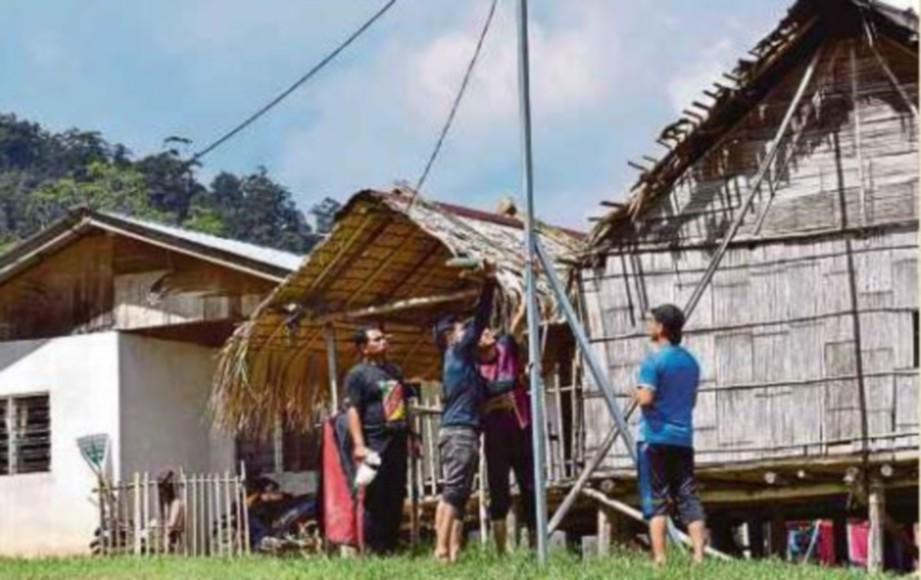 SUKARELAWAN mendirikan tiang untuk pemasangan lampu solar