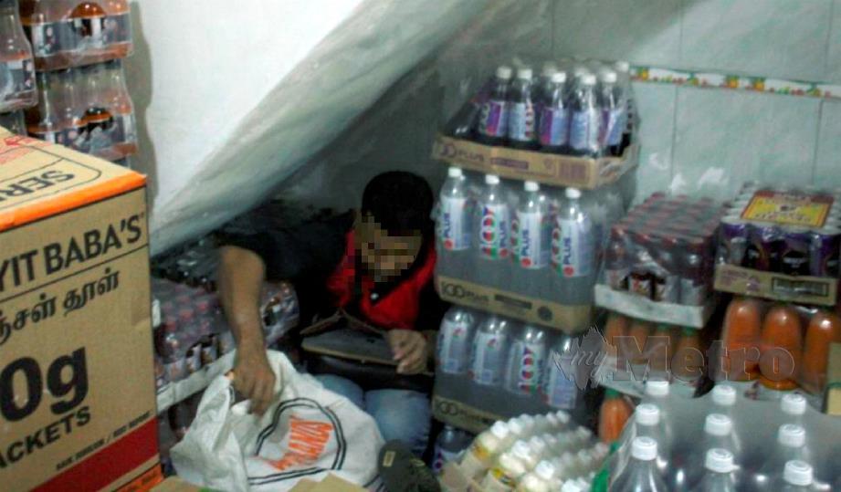 LELAKI warga Bangladesh yang bersembunyi di bawah tangga di sebalik timbunan kotak stok minuman di kedai serbaneka di Jalan Gurdwara, Georgetown, ditahan kerana tiada dokumen perjalanan. FOTO ihsan JIMPP.