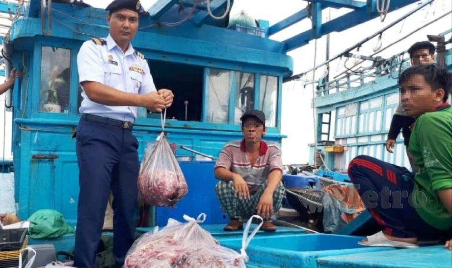 RASHIDILHADI menunjukkan sebahagian sotong dirampas selepas menahan tiga bot nelayan Vietnam di perairan Kuala Kemaman, Chukai, semalam. FOTO Rosli Ilham.