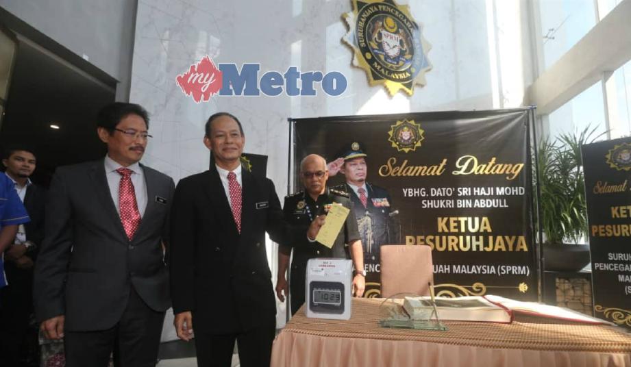 MOHD Shukri (tengah) mengetip kad perakam waktu tepat 10.29 pagi ketika melaporkan diri di Ibu Pejabat SPRM, Putrajaya, hari ini. FOTO Mohd Fadli Hamzah