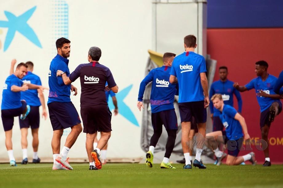 SUAREZ (tiga kiri) berbual dengan Valverde ketika sesi latihan semalam. — FOTO EPA