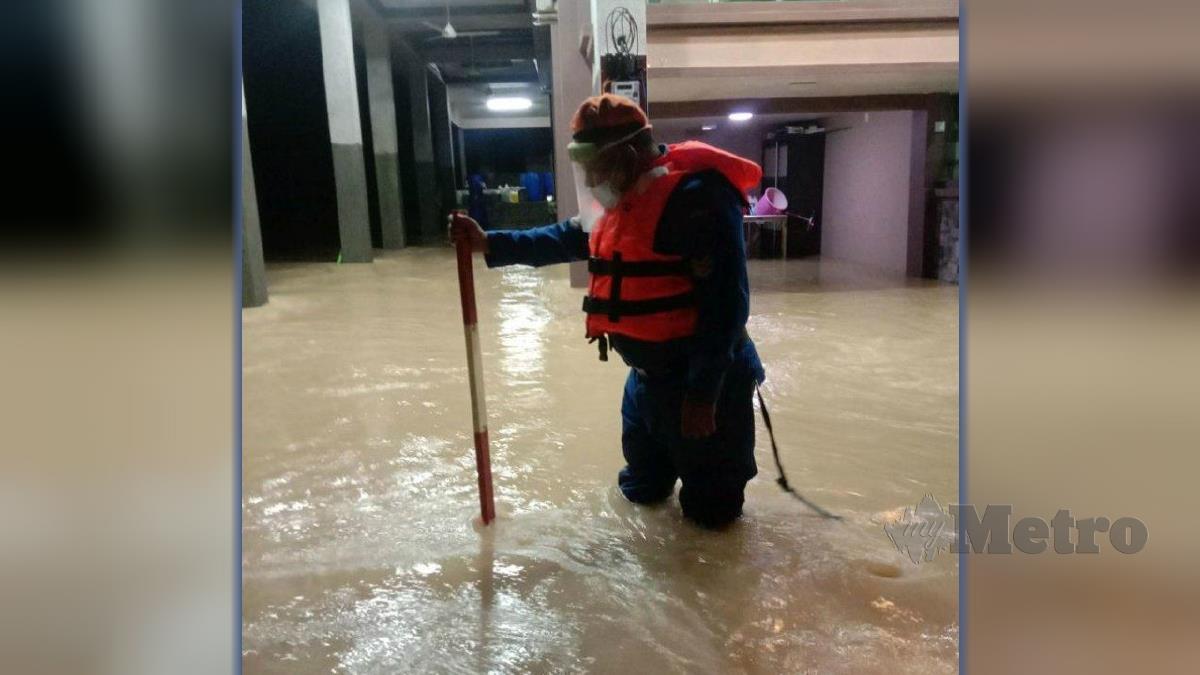 ANGGOTA APM Kulim menyukat paras air berikutan banjir kilat yang melanda daerah itu, semalam. FOTO Ihsan APM.