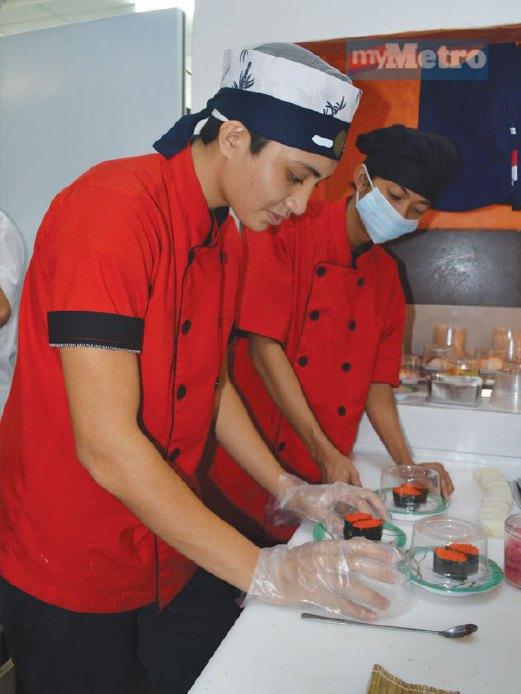 PEKERJA sedang menyiapkan hidangan sushi yang dipesan pelanggan.