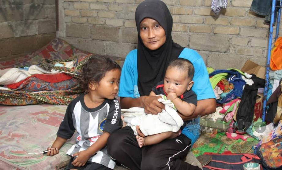 NORIZA bersama dua anaknya yang dibawa bersama ketika mencari besi buruk. FOTO Nik Abdullah Nik Omar.