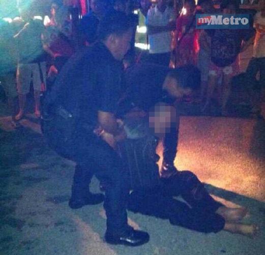 SUSPEK ditahan anggota polis di lokasi kejadian.