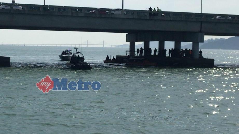 ANGGOTA pasukan mencari dan menyelamat berada di lokasi penemuan SUV putih yang terhumban ke laut di Jambatan Pulau Pinang, hari ini. FOTO Hadzlihady Hassan.