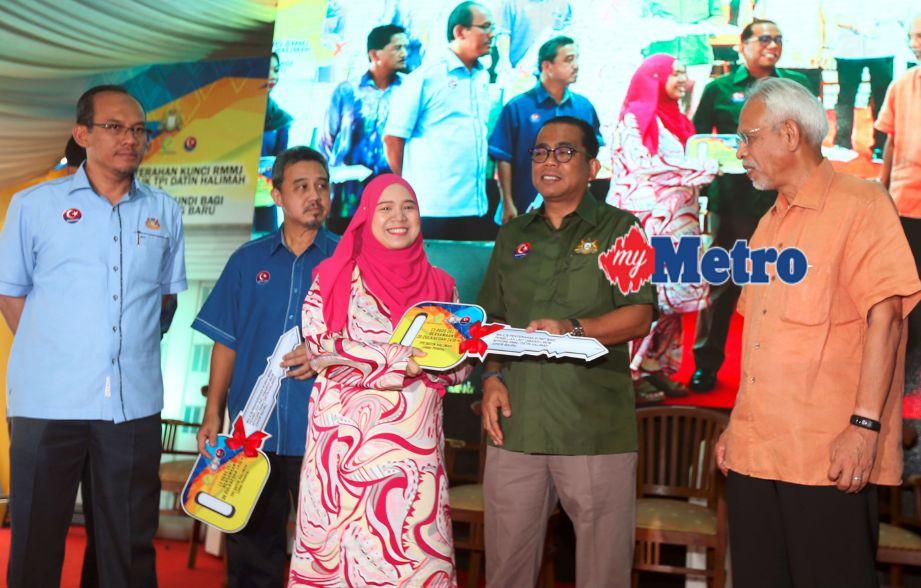 Mohamed Khaled menyampaikan replika kunci rumah kepada pemilik rumah sambil diperhatikan Md Jais (kiri), Ahli Parlimen Johor Bahru, Tan Sri Shahrir Abdul Samad (kanan) dan Pengarah Urusan PIJ Holdings, Rozan Mohd Sa'at (dua dari kiri) ketika majlis penyerahan kunci RMMJ kepada pemilik TPI Datin Halimah dan Majlis Cabutan Undi Pakej A TPI Stulang Baru. FOTO Hairul Anuar Abd Rahim