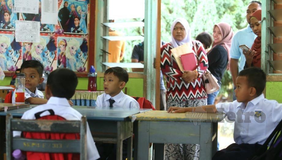 IBU bapa menemani anak masing-masing pada hari pertama persekolahan di Sekolah Kebangsaan Parit Bilal, Batu Pahat. FOTO Adi Safri.